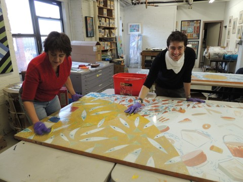 Rika Smith McNally and Rory Beerits of Cambridge Arts Council, cleaning the mural